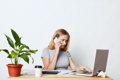 Female enterpreneur, being busy with work, keyboarding on laptop computer, calling her business partner while consulting something Stock Images