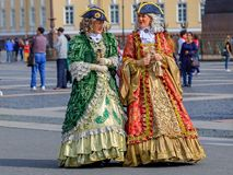 Female entertainers in period dresses awaiting tourists by the Hermitage Winter Palace on Palace Square Saint Petersburg, Russia. Saint Petersburg, Russia royalty free stock photography