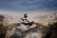 Female entrepreneur above cliff with partner Royalty Free Stock Photos