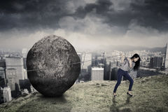Female entrepreneur with big stone on the hill. Young female entrepreneur is pulling big stone with a chain while walking on the hill Royalty Free Stock Photography