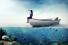 Female entrepreneur with binoculars on boat. Image of a female entrepreneur looking through binoculars while sitting on a boat at the sea Stock Images