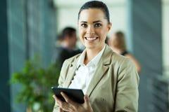 Female entrepreneur. Cheerful female entrepreneur using tablet computer in modern office Stock Image