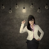 Female entrepreneur choosing bright bulb Royalty Free Stock Photos