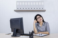 Female entrepreneur daydreaming in office. Portrait of female entrepreneur daydreaming in the office while sitting in front of computer Royalty Free Stock Photos