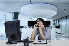 Female entrepreneur daydreaming with smartphone. Portrait of female entrepreneur daydreaming while listening on smartphone in the office Stock Images