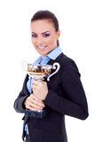 Female entrepreneur holding a trophy. Portrait of a joyful young female entrepreneur holding a trophy against white background Stock Photography