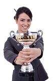 Female entrepreneur holding a trophy. Portrait of a joyful young female entrepreneur holding a trophy against white background Royalty Free Stock Photography