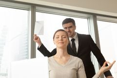 Female entrepreneur ignoring problems at work. Funny young women with peaceful facial expression meditating at workplace in office, angry boss with documents in Royalty Free Stock Photo