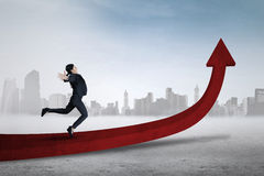 Female entrepreneur jumping on red arrow Stock Photo