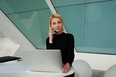 Female entrepreneur looking at the camera while phoning via mobile smart phone Stock Photography