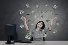 Female entrepreneur looking money. Female entrepreneur raising her hands while looking money flying over her head Royalty Free Stock Photos
