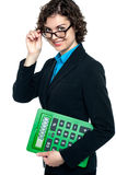 Female entrepreneur looking at you. Lady executive with a calculator in hand adjusting her spectacles stock illustration