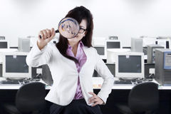 Female entrepreneur with magnifier in office Royalty Free Stock Images
