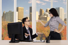 Female entrepreneur pointing to her subordinate Stock Photo