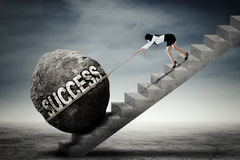 Female entrepreneur pulling boulder on stairs. Young female entrepreneur climbing a stairs while pulling a boulder with success word Royalty Free Stock Image