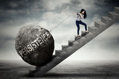 Female entrepreneur pulling persistence word on stair Royalty Free Stock Images