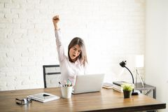 Excited woman in an office. Female entrepreneur screaming of happiness and raising her arm as a sign of sucess Stock Images