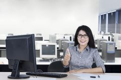 Female entrepreneur showing Ok sign in the office. Portrait of female entrepreneur showing OK sign with her thumb while working in the office Royalty Free Stock Image