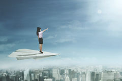 Female entrepreneur stands on paper plane Stock Photography