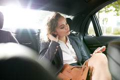 Female entrepreneur travelling to work in a luxury car Stock Image