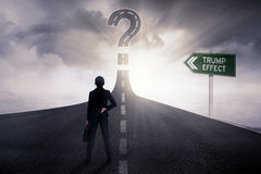 Female entrepreneur with Trump Effect word at road. Back view of female entrepreneur standing on the road with Trump Effect word on the road sign and a question Royalty Free Stock Photos