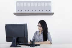 Female entrepreneur working with computer. Portrait of female entrepreneur working with computer while sitting in the office room Stock Photography