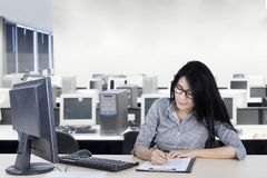 Female entrepreneur writing on the clipboard. Picture of female entrepreneur writing on the clipboard by using a pen while sitting in the office Stock Images
