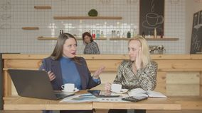 Businesswomen drinking coffee talking in cafeteria. Female entrepreneurs sitting at cafe table drinking coffee, discussing tax issues, sharing business ideas stock video