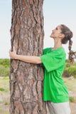 Female environmental activist hugging tree trunk Stock Photo