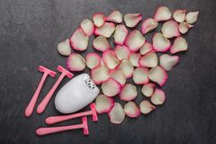 Close-up of a female epilator and four disposable razors with rose petals. royalty free stock photography