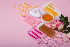 Epilator, disposable razor, wax, wax strips with roses on a pink background, space for text. stock photography