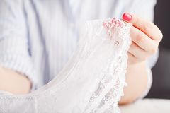 Female erotic fashionable lace panties or lingerie on wooden background with hands stock images