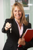 Female Estate Agent Handing Over Keys. Portrait Of Female Estate Agent In Office Handing Over Keys Royalty Free Stock Photo