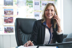 Female Estate Agent On Phone In Office Royalty Free Stock Photography