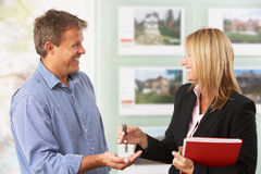 Female Estate Handing Over Keys Of New Home. To Client Stock Image