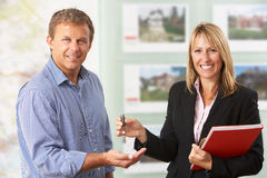Female Estate Handing Over Keys Of New Home. To Client Royalty Free Stock Images