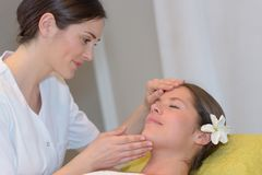Female esthetician massaging head and face young woman Stock Photo