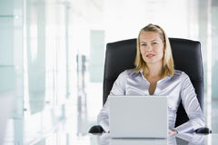 Female executive at desk. With laptop looking to camera stock photos