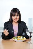 Female Executive Eating Fresh Vegetable Salad. Portrait of smiling female executive having fresh vegetable salad in office Stock Photography