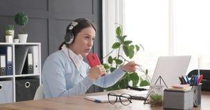 Female executive enjoying music disturbed by interruption stock footage