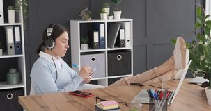 Female executive with feet up on desk while listening music. Businesswoman relaxing with feet up on desk while listening music and writing to do list stock video