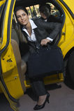 Female Executive Getting Out Of Taxi royalty free stock photo