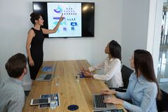 Female executive giving presentation to her colleagues in conference room. At office stock image
