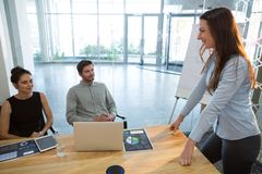 Female executive giving presentation to her colleagues in conference room. At office royalty free stock photo