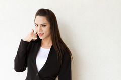 Female executive with hand sign of phone contact Royalty Free Stock Photos