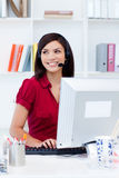 Female executive with headset on at her desk Royalty Free Stock Images