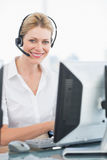 Female executive with headset using computer at desk Royalty Free Stock Photography