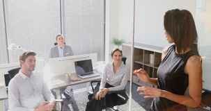 Female executive with his colleagues discussing over glass board 4k. Female executive with his colleagues discussing over glass board in office 4k stock footage