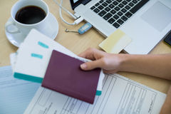 Female executive holding tickets and passport at her desk Stock Image