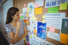Female executive looking at bulletin board Stock Images